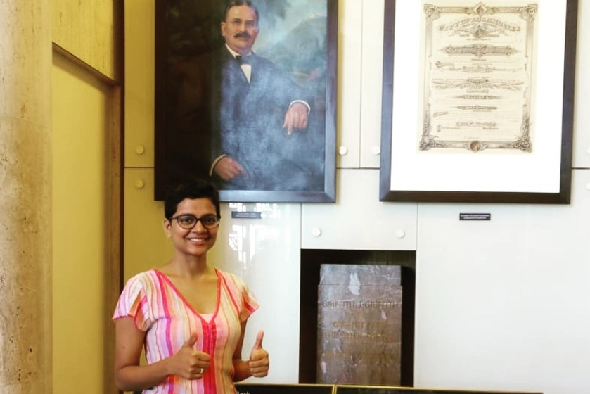 A smiling Sharmila posing in front of a painting of Ben Franklin with her thumbs up