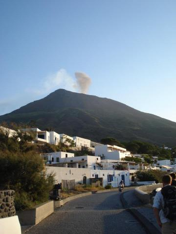 A picturesque white village with the looming Stromboli volcano in the background.