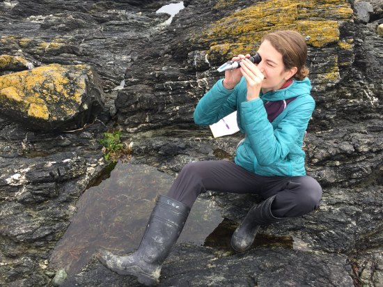 Here sits Alyssa on a seaside rock, rain boots on her feat, looking through a viewfinder for organisms.