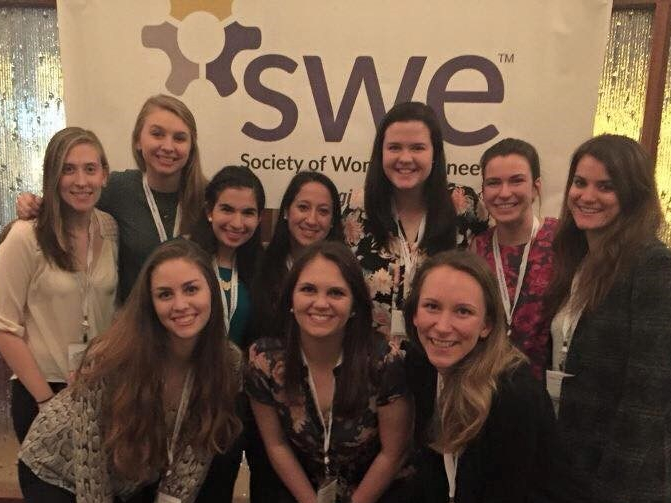 Photo of Ali and friends standing in front of the Society of Women Engineers sign.