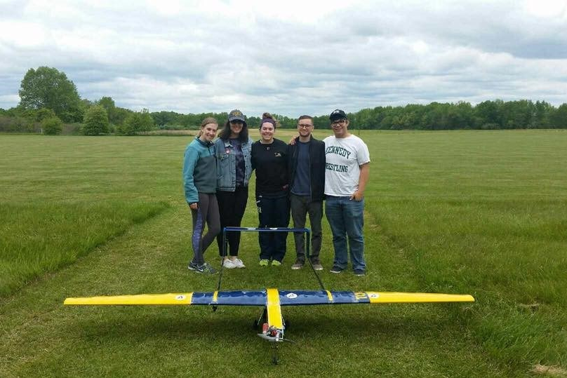 A photo of Ali with her group in a green field standing behind a blue and yellow plane.