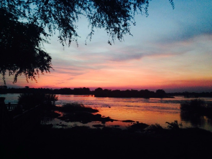 Sunrise has begun over the Zambezi River, painting the sky night-purple to peach cream to day-blue. The wide river mirrors the sky, but the currents swirl the colors like an artist's palette.