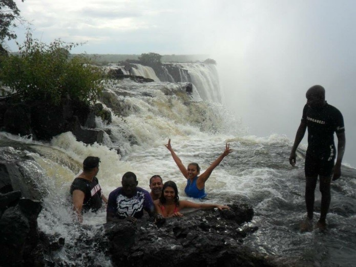 Aniska smiling for the camera with her friends and loved ones, while they swim on a ledge, near a waterfall.