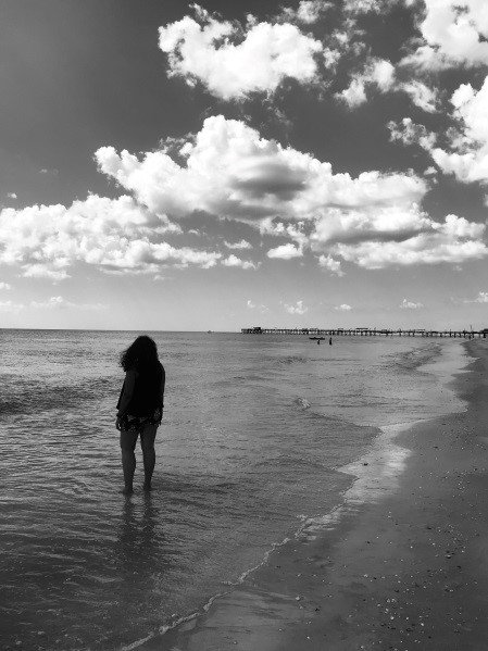Black and white photo of Aniska with her feet in the water at the beach.