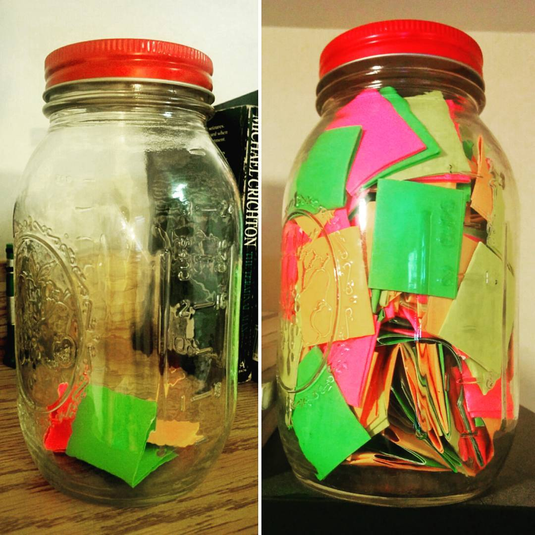 Image of a mason jar filled with 365 days worth of positive thoughts on colorful paper.